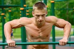 Allenamento muscolare della via di pratica dell'uomo in una palestra all'aperto Immagine Stock Libera da Diritti
