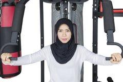 Allenamento musulmano della donna sull'attrezzatura di forma fisica Immagini Stock Libere da Diritti