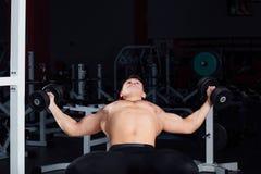 Allenamento professionale del culturista con il bilanciere alla palestra Grande addestramento muscolare sicuro dell'uomo motivazi Fotografie Stock
