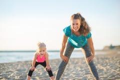 Allenamento sano della neonata e della madre sulla spiaggia Immagine Stock