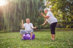 Allenamento senior della gente - uomo e donna che fanno insieme il exe di forma fisica Fotografie Stock Libere da Diritti