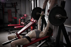 Allenamento sexy della ragazza di forma fisica con il bilanciere nella palestra Donna castana nell'usura di sport con l'ente musc Fotografia Stock