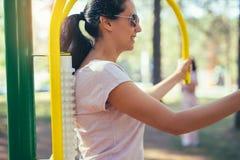 Allenamento sorridente della donna al simulatore del massaggiatore Fotografia Stock