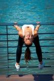 Allenamento sorridente della giovane donna su strainght e sul outd muscolare di configurazione Fotografie Stock
