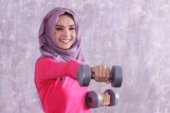 Allenamento sportivo della donna del bello hijab facendo uso della testa di legno Fotografia Stock