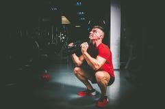 Allenamento trasversale dell'uomo di forma fisica con il piatto del peso del bilanciere nella palestra Immagini Stock