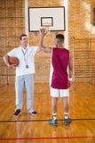 Allenatore alto fiving con il giocatore di pallacanestro Fotografia Stock