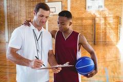 Allenatore che discute con il giocatore di pallacanestro Fotografia Stock