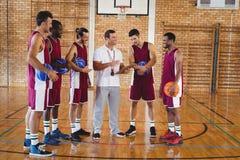 Allenatore che interagisce con i giocatori di pallacanestro Fotografia Stock