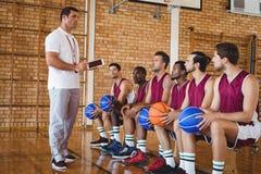 Allenatore che interagisce con i giocatori di pallacanestro Fotografia Stock Libera da Diritti