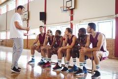 Allenatore che interagisce con i giocatori di pallacanestro Immagini Stock