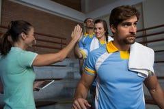 Allenatore dare alto--cinque al giocatore di pallavolo femminile Fotografia Stock