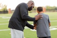Allenatore di football americano che forma un giovane atleta immagini stock libere da diritti