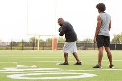 Allenatore di football americano che forma un giovane atleta immagini stock