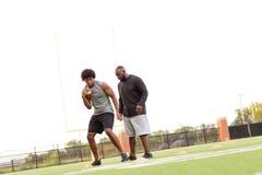 Allenatore di football americano che forma un giovane atleta fotografia stock