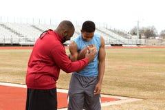Allenatore di football americano che prepara un atleta Fotografie Stock