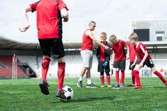 Allenatore di football americano Working con i bambini fotografie stock