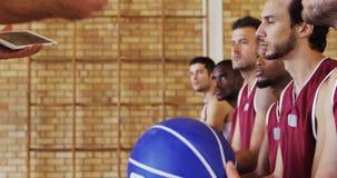 Allenatore di pallacanestro che assiste i giocatori sulla compressa digitale stock footage