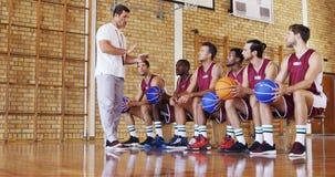 Allenatore di pallacanestro che assiste i giocatori sulla compressa digitale archivi video
