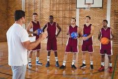 Allenatore di pallacanestro che interagisce con i giocatori Immagine Stock