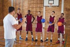 Allenatore di pallacanestro che interagisce con i giocatori Fotografie Stock Libere da Diritti