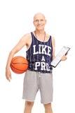 Allenatore di pallacanestro senior che tiene una lavagna per appunti Immagine Stock