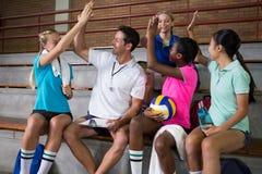 Allenatore di pallavolo che dà livello cinque ai giocatori femminili Fotografia Stock Libera da Diritti