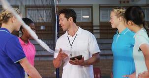 Allenatore di pallavolo che discute con i giocatori femminili sulla compressa digitale 4k video d archivio
