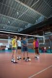 Allenatore di pallavolo che discute sopra la lavagna per appunti con il giocatore femminile Fotografia Stock Libera da Diritti