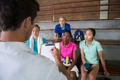 Allenatore di pallavolo che discute sopra la lavagna per appunti con il giocatore femminile Fotografie Stock Libere da Diritti