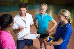 Allenatore di pallavolo che parla con giocatori femminili Immagini Stock