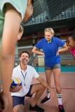 Allenatore di pallavolo che parla con giocatori femminili Fotografia Stock