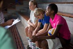 Allenatore di pallavolo che parla con giocatori femminili Fotografia Stock Libera da Diritti