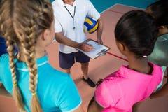 Allenatore di pallavolo che parla con giocatori femminili Immagine Stock