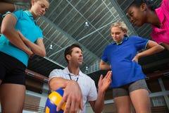 Allenatore di pallavolo che parla con giocatori femminili Immagine Stock Libera da Diritti