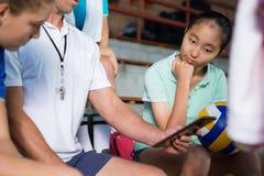 Allenatore di pallavolo che parla con giocatori femminili sopra la compressa digitale Fotografia Stock