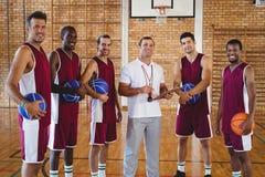 Allenatore e giocatore di pallacanestro sorridenti che stanno nella corte Fotografie Stock