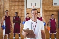 Allenatore e giocatore di pallacanestro sorridenti che stanno nella corte Fotografia Stock Libera da Diritti