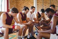 Allenatore e giocatori di pallacanestro che per mezzo della compressa digitale Immagini Stock Libere da Diritti