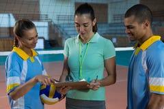 Allenatore femminile che discute con i giocatori di pallavolo Fotografia Stock