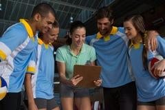 Allenatore femminile che spiega ai giocatori di pallavolo alla corte Fotografia Stock