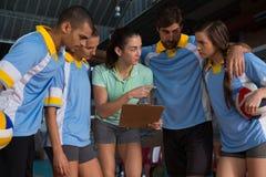 Allenatore femminile che sta con i giocatori di pallavolo Fotografia Stock