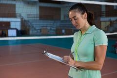 Allenatore femminile scrittura di pallavolo sulla lavagna per appunti Fotografie Stock