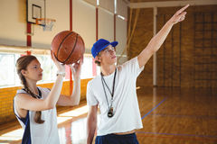 Allenatore maschio che consiglia giocatore di pallacanestro femminile Fotografie Stock Libere da Diritti