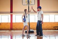 Allenatore maschio che fa livello cinque con il giocatore di pallacanestro femminile Fotografia Stock