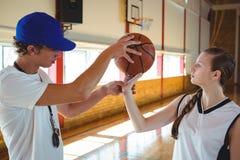 Allenatore maschio che forma giocatore di pallacanestro femminile Fotografia Stock