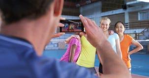Allenatore maschio che prende immagine del giocatore femminile con il telefono cellulare 4k video d archivio