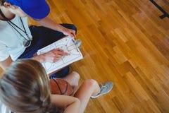 Allenatore maschio che spiega diagramma al giocatore di pallacanestro femminile Fotografia Stock Libera da Diritti
