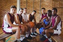 Allenatore sicuro e giocatore di pallacanestro che si siedono sul banco Immagini Stock Libere da Diritti