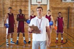 Allenatore sicuro e giocatore di pallacanestro che stanno nella corte Fotografia Stock